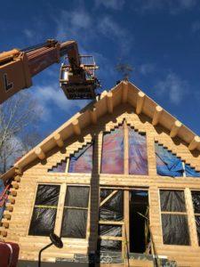 A lull machine lifts roof system materials on a Katahdin Cedar Log Home