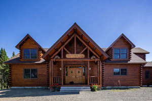 Whimsical carved otters welcome the entrance to Katahdin Cedar Log Home